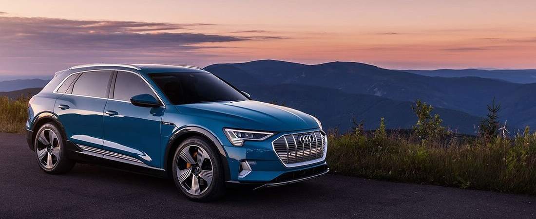 side front view of blue Audi e-tron at dusk with mountains in the background