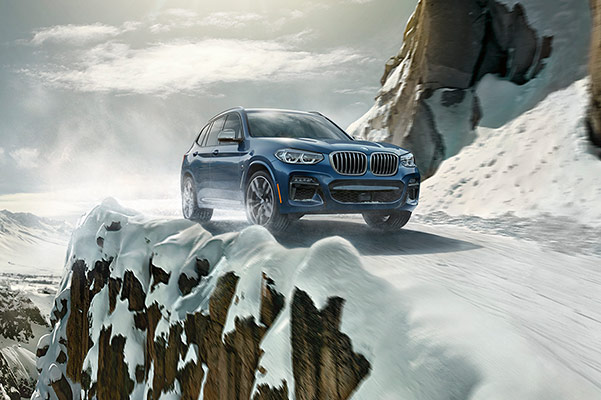 blue BMW x3 suv driving on a snowy mountain side road