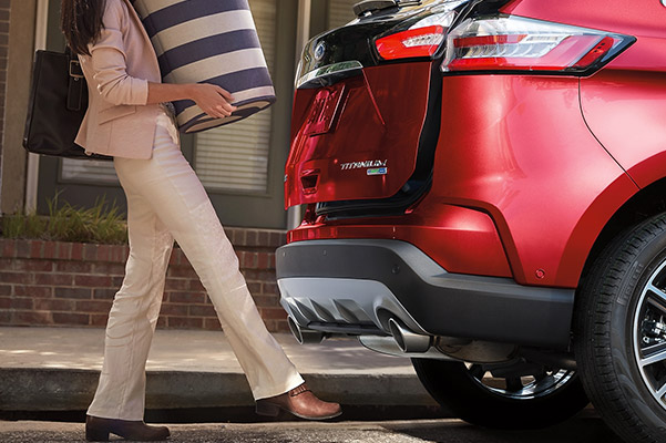 a woman with bags on her hands opening the trunk of a Ford edge with her foot sensor