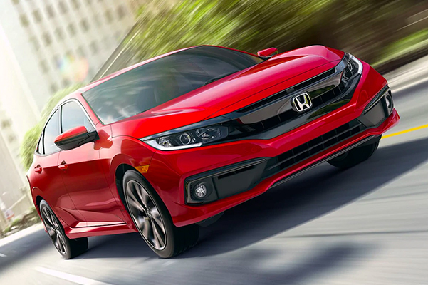 frontal view of red honda civic vehicle driving at high speed through the city