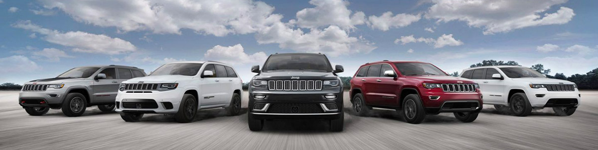 2020 lineup of Jeep Grand Cherokees driving down a road with blue skies
