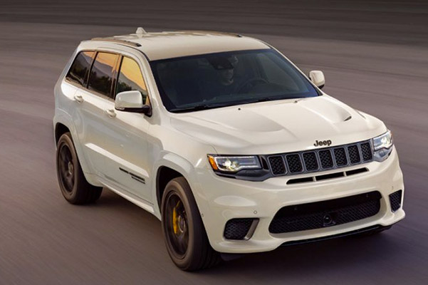 Front view of a white 2020 Jeep Grand Cherokee driving down a road