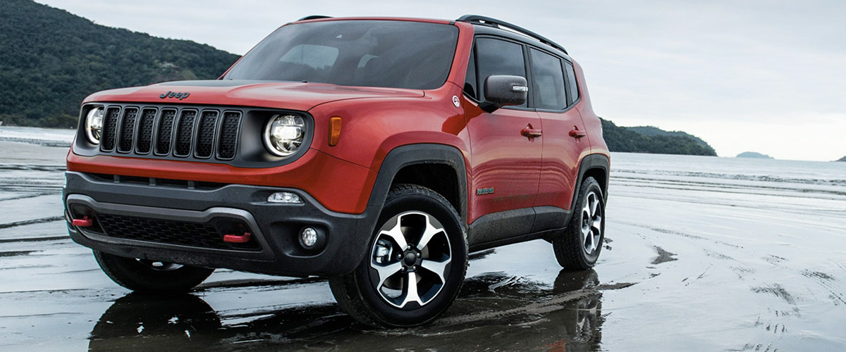 frontal view of a red Jeep renegade suv on the beach