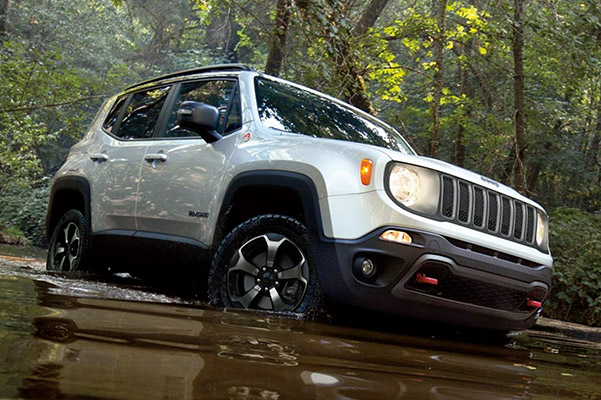 a white Jeep Renegade crossing a pond through the middle of the jungle