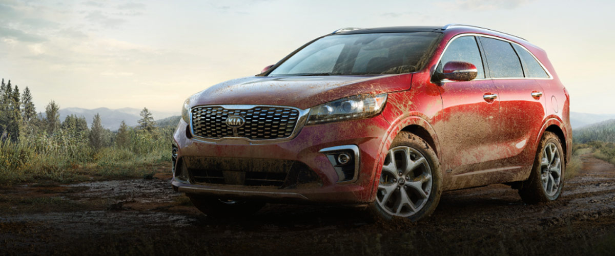 side view of Red Kia sorento suv with mud all over the place parked on a dirt road