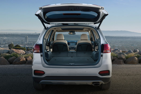 rear view of kia sorento suv with the back door open with mountains in the background