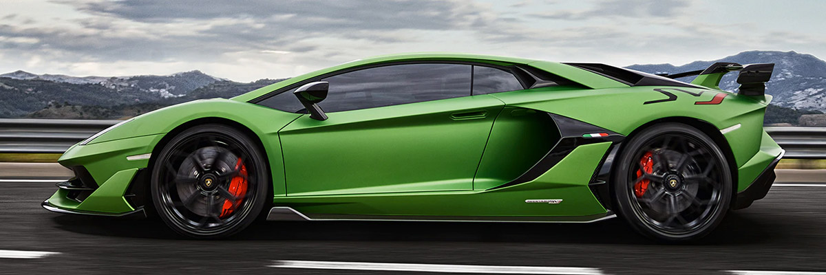 Green 2020 Lamborghini Aventador with black rims going at high speed on a racetrack