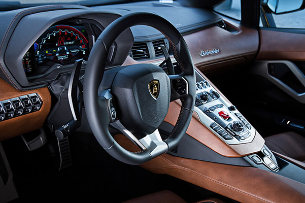 Interior view of 2020 Lamborghini Aventador showcasing the steering Wheel, digital display and brown leather interior