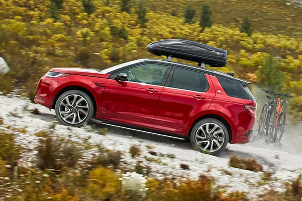 red Land Rover Discovery sport suv going up hill on a mountain