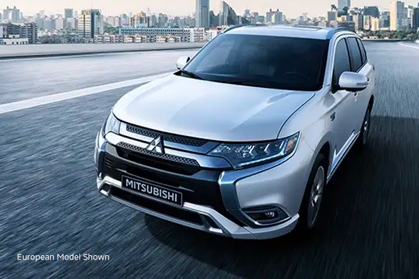 Front side view of a silver 2020 Mitsubishi Outlander PHEV SUV driving on a city highway.