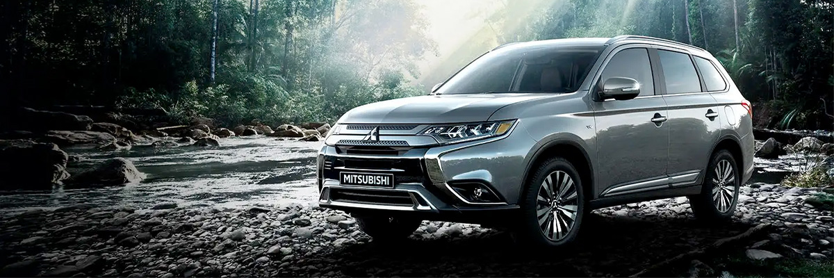 Front side exterior view of a 2020 Mitsubishi Outlander SUV parked beside a creek in the jungle.