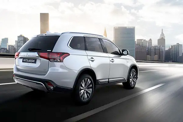 Rear exterior view of a white 2020 Mitsubishi Outlander SUV driving in the city.