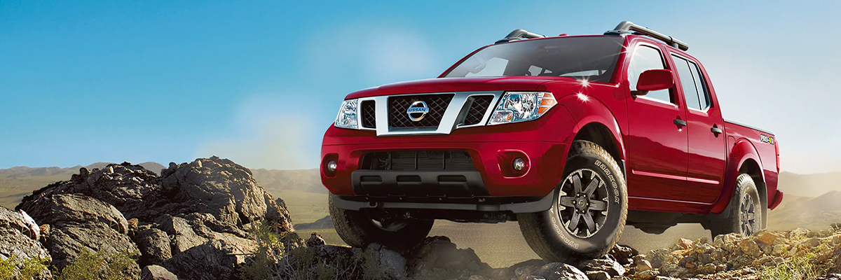 2020 Nissan Frontier midsize pickup truck in Cayenne Red Metallic on a rocky plain