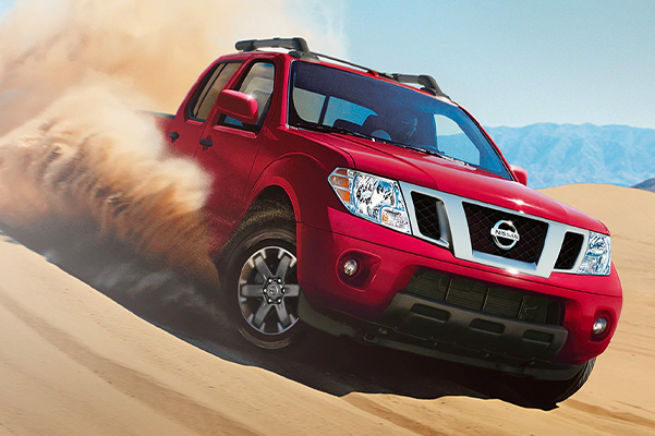 2020 Nissan Frontier in Cayenne Red Metallic driving down a dune face