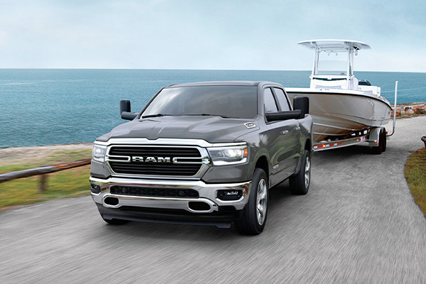 A 2020 Ram 1500 being driven on a seaside road while towing a boat.
