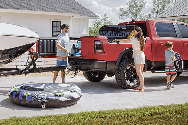 A 2020 Ram 1500 parked in a driveway with a boat on a trailer hitch as a family loads boating gear into the bed.