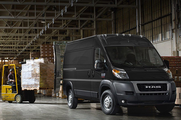 A 2020 Ram ProMaster Cargo Van in a warehouse with a forklift loading a pallet of boxes through the rear doors.