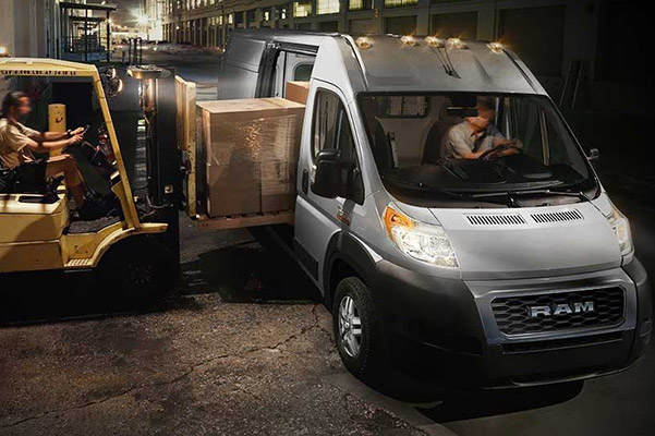 A 2020 Ram ProMaster Cargo Van with a forklift loading a pallet of boxes through the side door.