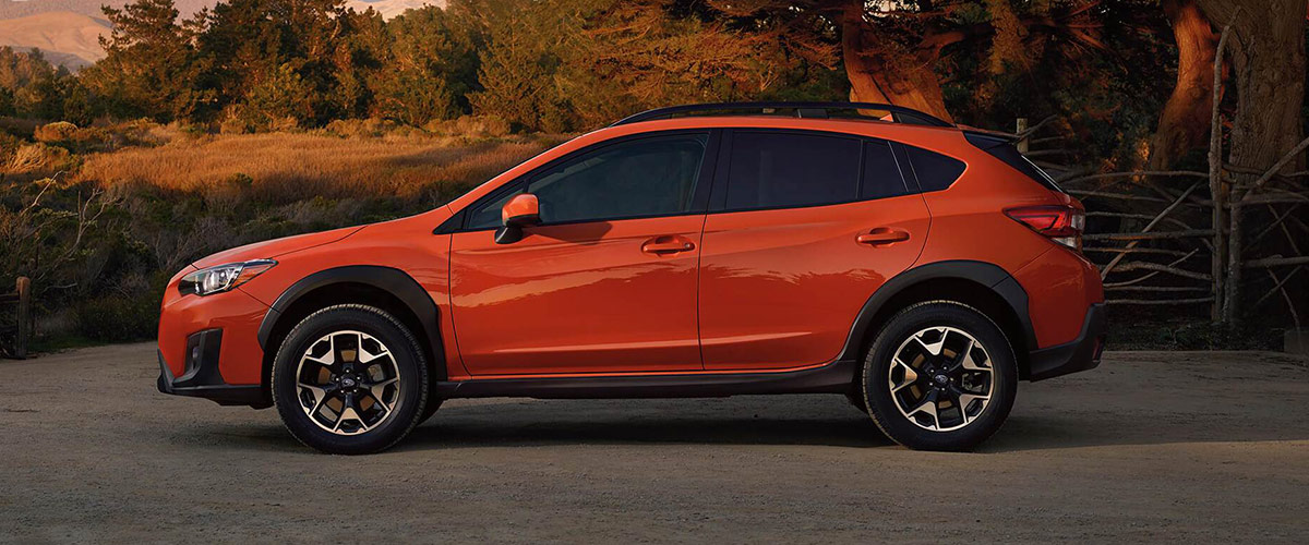 side view of orange color Subaru Crosstrek crossover with a sunset background near a forest