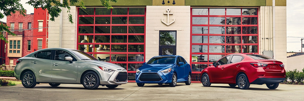 Image of a white 2020 Toyota Yaris, a blue 2020 Toyota Yaris and red 2020 Toyota Yaris parked facing eachother in front of a building