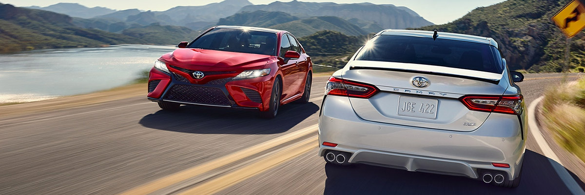 A red 2020 Toyota Camry driving past a white 2020 Toyota Camry going the opposite direction