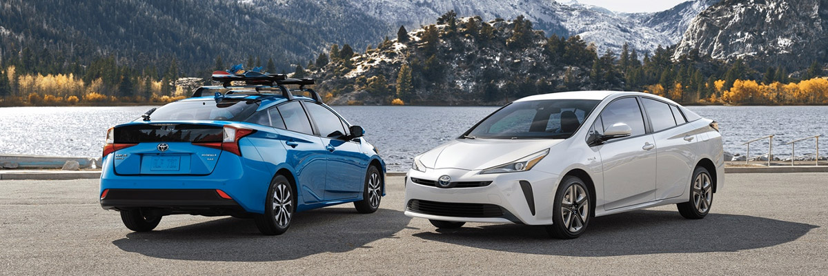 A blue 2020 Toyota Prius parked backwards with a white 2020 Toyota Prius parked forwards right next to it with water and mountains in the background