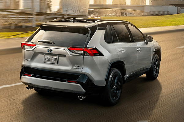Exterior rear view of a 2020 Toyota RAV4 driving down a road