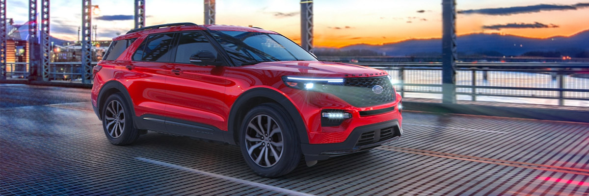 red ford explorer suv  with headlights on crossing a steel made bridge with a sunset in the background