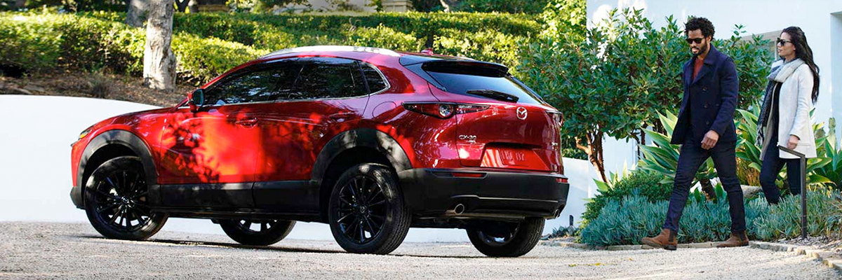 Young couple walkin up to their new red Mazda CX-30