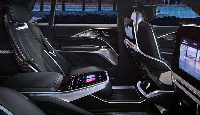interior shot of Cadillac LYRIQ EV featuring back sits with digital screens and digital controller