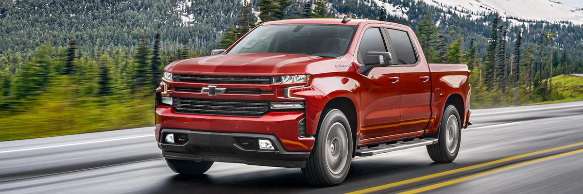 red chevrolet silverado pick up truck on a road at a high speed with trees and snow mountains around it