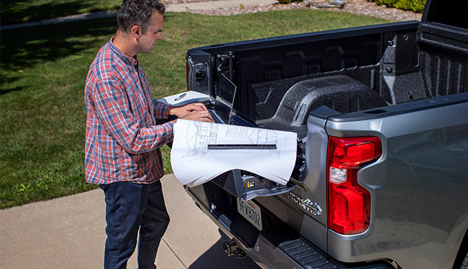a man using his laptop on top of the Multi-Flex Tailgate from the 2021 chevrolet silverado