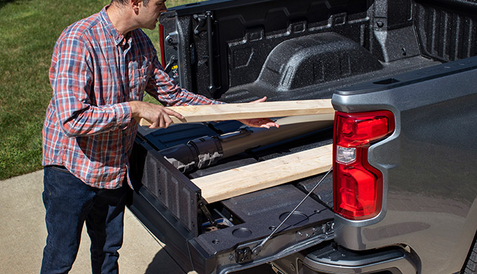 a man pulling lumber from the 2021 chevrolet silverado Multi-Flex Tailgate