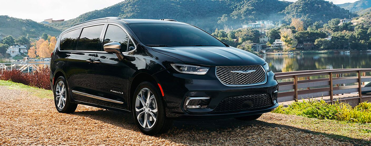 The 2021 Chrysler Pacifica parked in front of a lake with a mountain in the distance.
