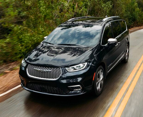 The 2021 Chrysler Pacifica being driven on a curving road.
