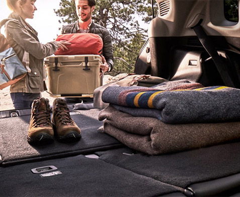 The cargo area of the 2021 Jeep Compass with both rear seats folded to accommodate hiking shoes and blankets.