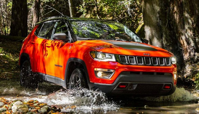 The 2021 Jeep Compass fording a stream in the woods.