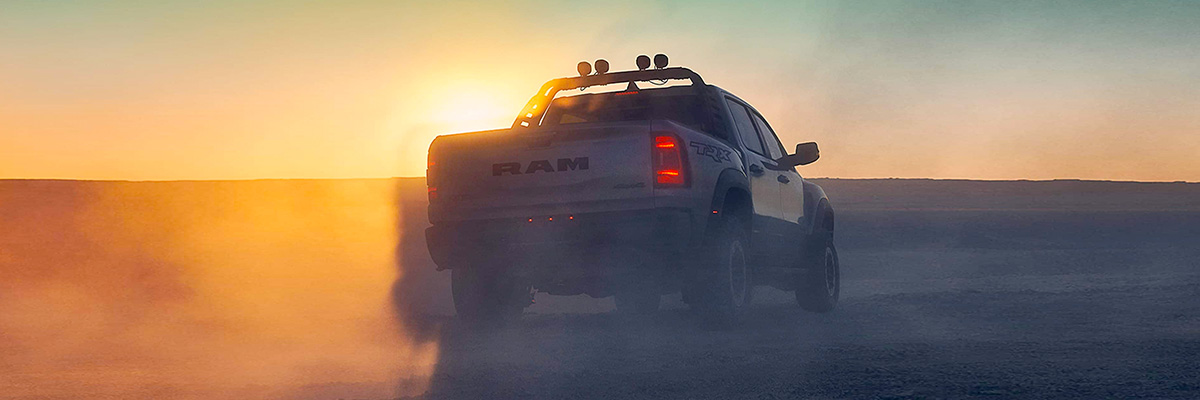 Display A rear view of the 2021 Ram 1500 TRX silhouetted against a sunset.