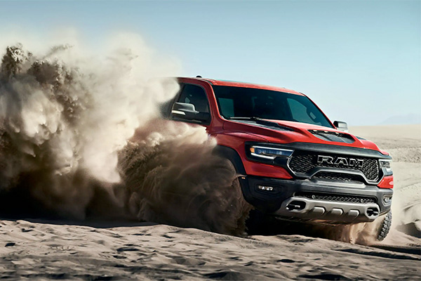 The 2021 Ram 1500 TRX churning up clouds of sand from its wheels as it is driven over a dune.
