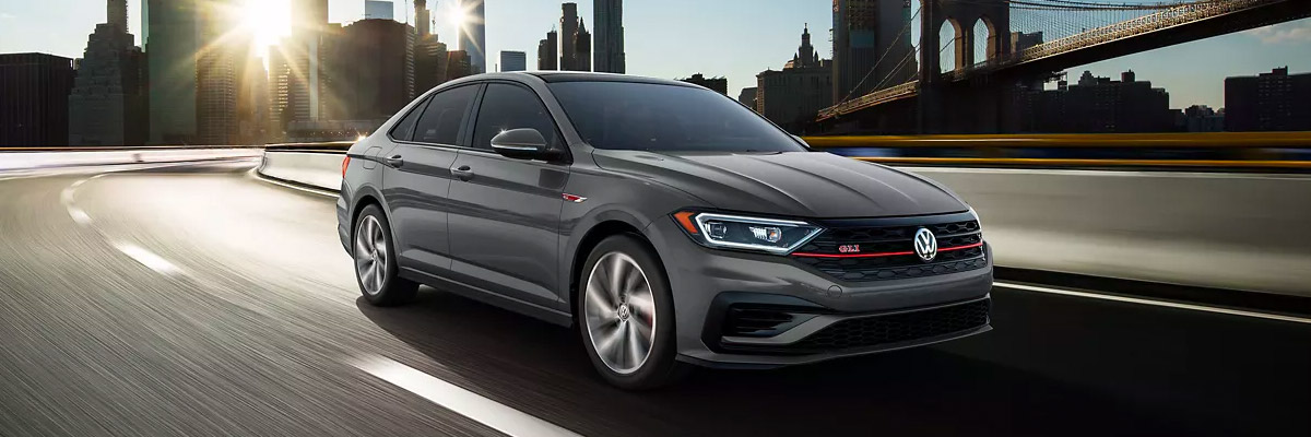 Jetta GLI in Pure Gray driving away from the city.