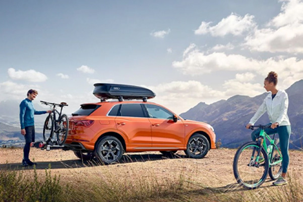 Two bikers next to Audi Q3 with mountian range background