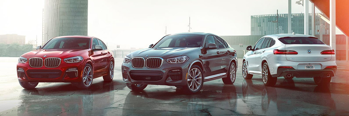 BMW X4 suv line up parked on concrete with architectural buildings in the background