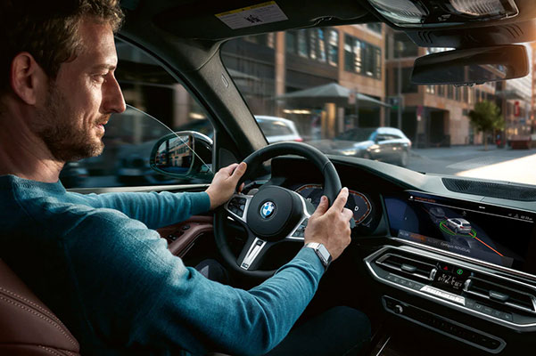 a man driving a BMW x5 and looking at the digital screen showcasing Digital guardrails.