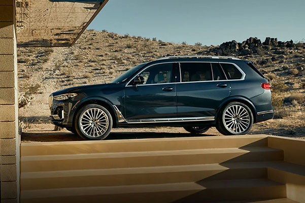 side view of BMW X7 suv on a dessert setting background