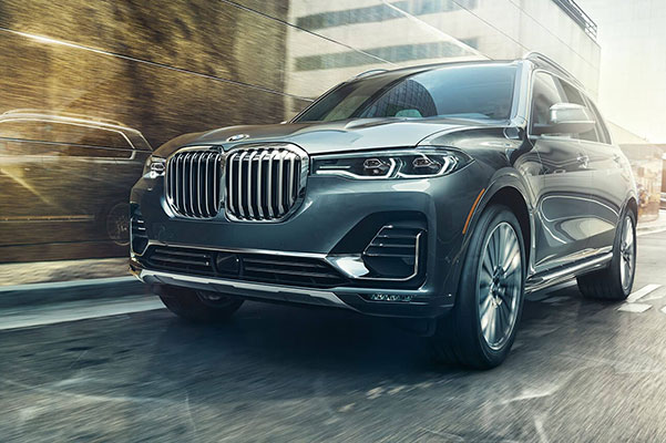 front side of a grey BMW X7 suv cruising through buildings in the middle of a city
