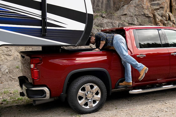 Man attaching trailer to 2021 Chevy Silverado HD bed