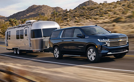 blue Chevrolet suburban suv towing a trailer on the road on a desert scenery