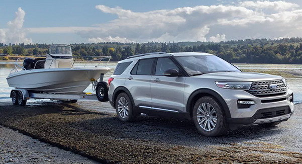A 2021 Ford Explorer backing a boat and boat trailer into the water
