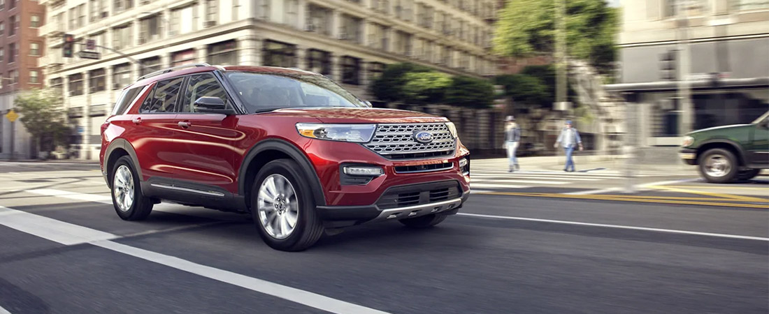 A 2021 Ford Explorer Limited in Rapid Red being driven down a city street