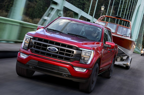 2021 F-150 in red towing boat over bridge